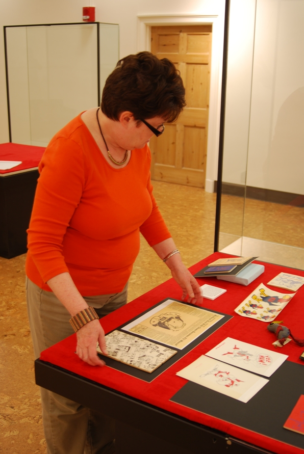 Photograph of University Archivist Becky Schulte positioning an item on mat board within the case