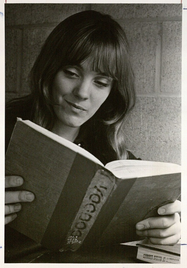 Photograph of a female KU student reading book about voodoo, 1970