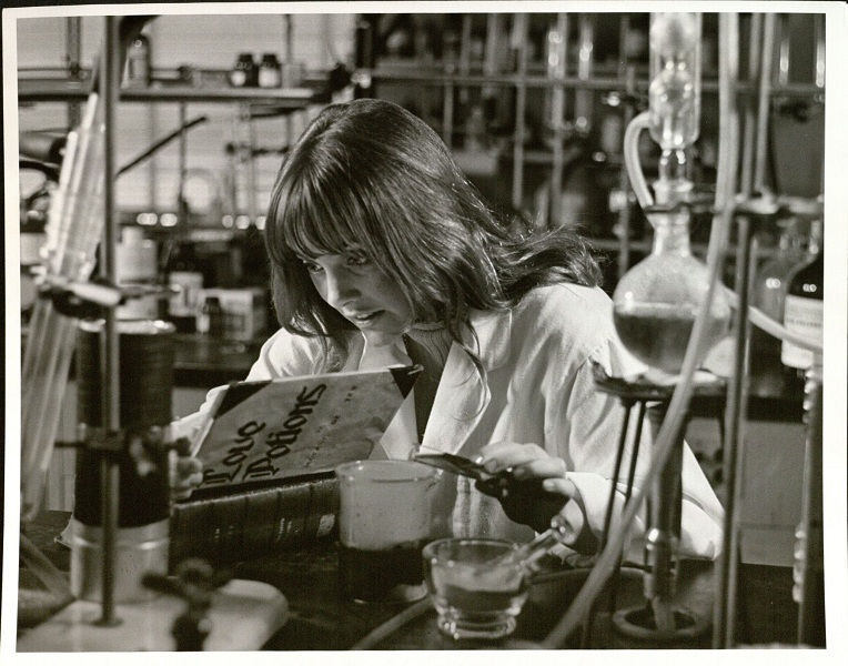 Photograph of a female KU student mixing a love potion, 1970