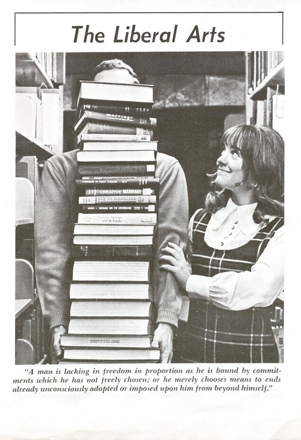 Photograph of a female KU student with the object of her affection behind a stack of books, 1970