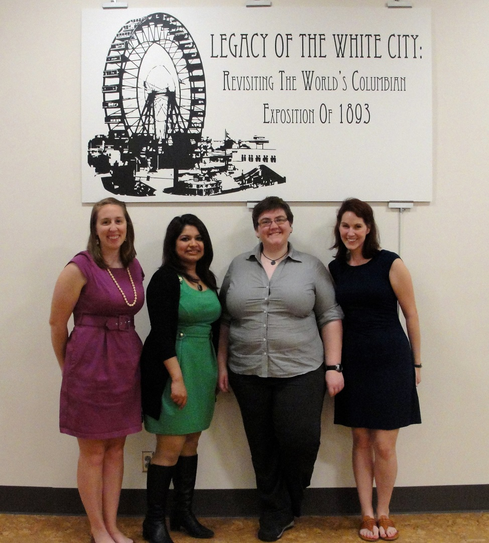 Image of the four exhibition curators in front of the exhibition sign