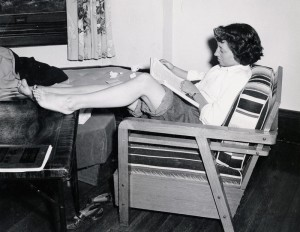 Photograph of student studying with bare feet, 1950s.