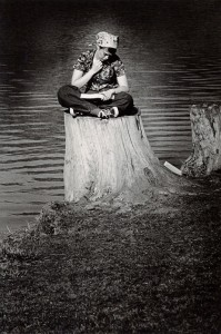 Photograph of a student studying on a stump, 1975-1976.