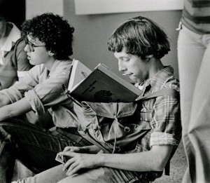 Photograph of student studying on top of backpack, 1976-1977.