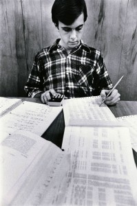 Photograph of student studying with calculator and printouts, 1979-1980.
