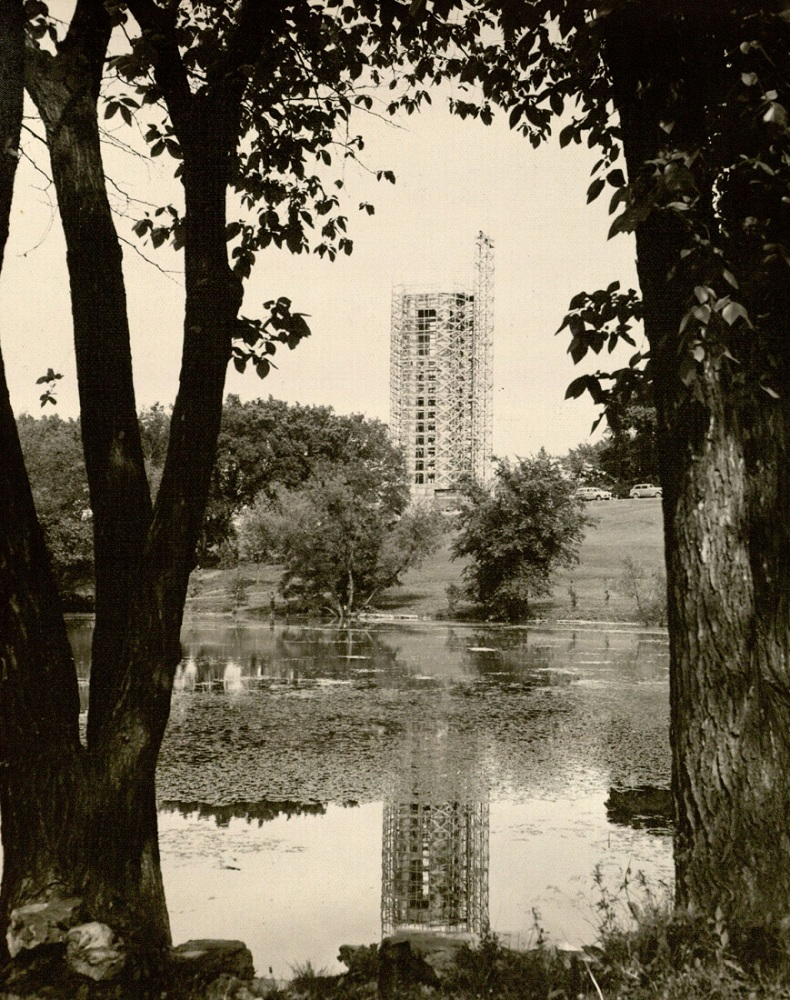 Photograph of the campanile under construction from across Potter Lake, 1950