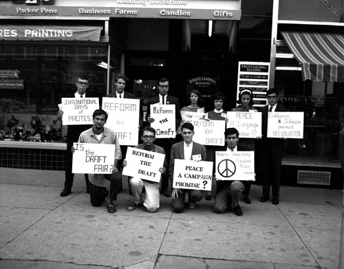 Photograph of Vietnam protestors with signs in front of a store on Massachusetts Street, 1965