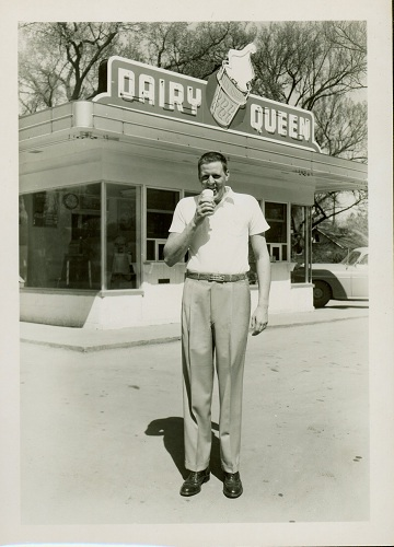 Photograph of Clyde Lovellette stands in front of a Dairy Queen eating an ice cream cone, 1952