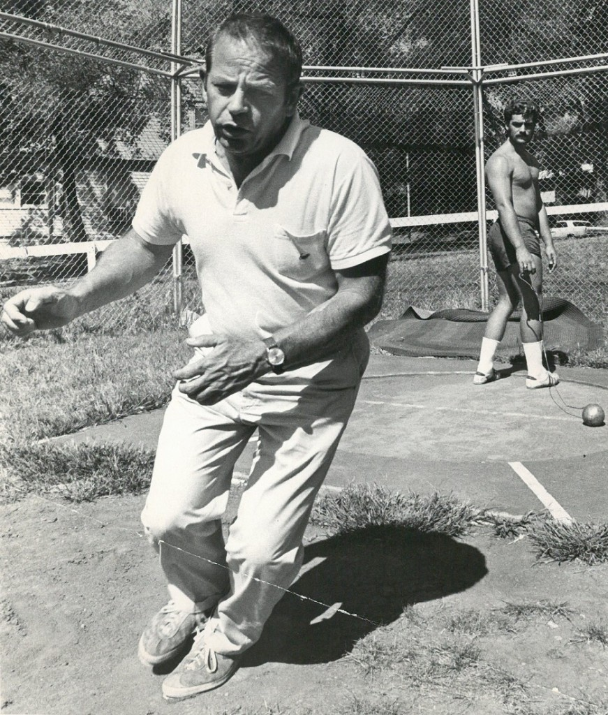 Photograph of Coach Bob Timmons instructing a shot-put athlete during practice