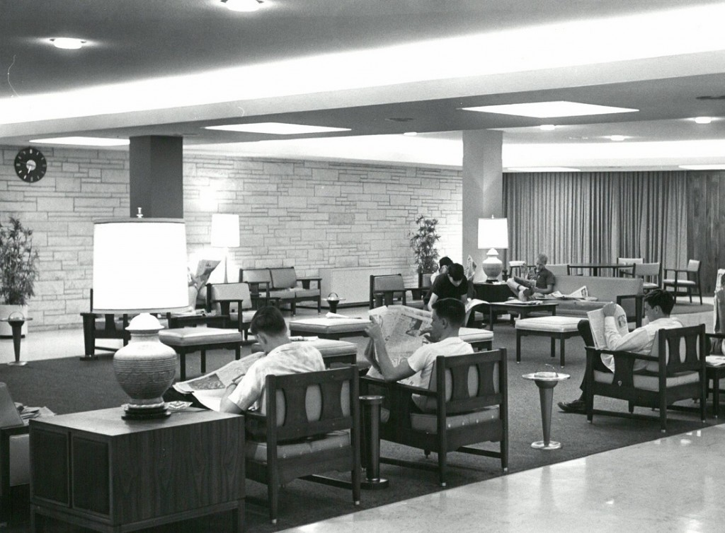 Photograph of McCollum Hall residents reading newspapers in the main lounge, 1965