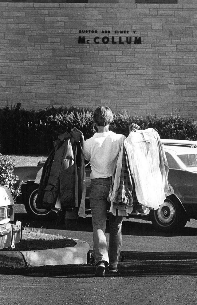 Photograph of a student carrying clothes into McCollum Hall, 1978/1979