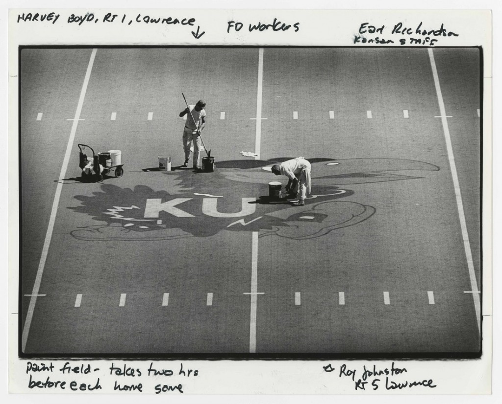 Photograph of Facilities workers painting a Jayhawk on the field at Memorial Stadium, 1980s
