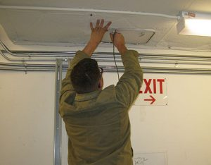 Man placing datalogger in vent, Spencer Research Library, University of Kansas.
