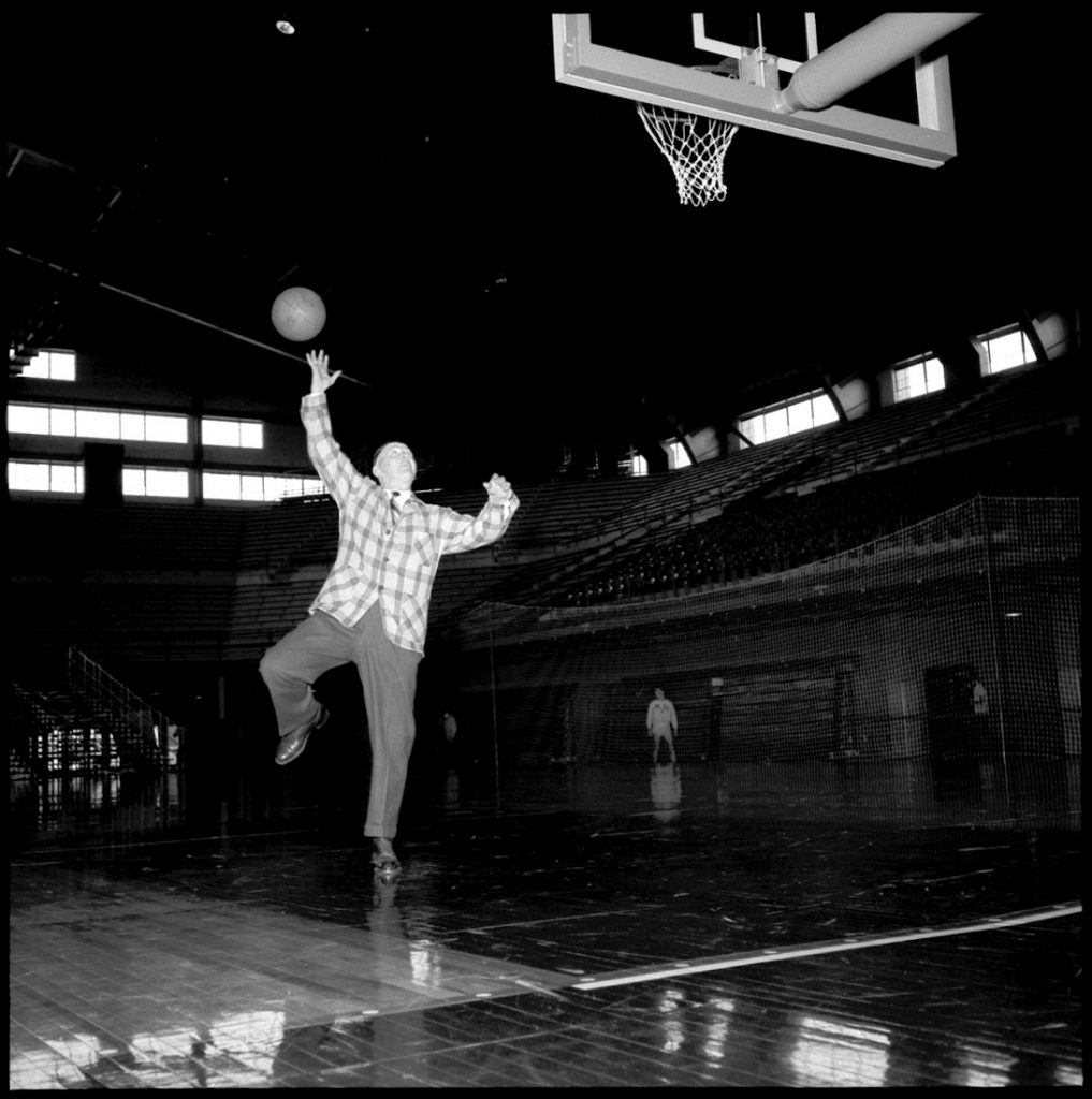 Photograph of Phog Allen shooting a layup in Allen Fieldhouse, 1955
