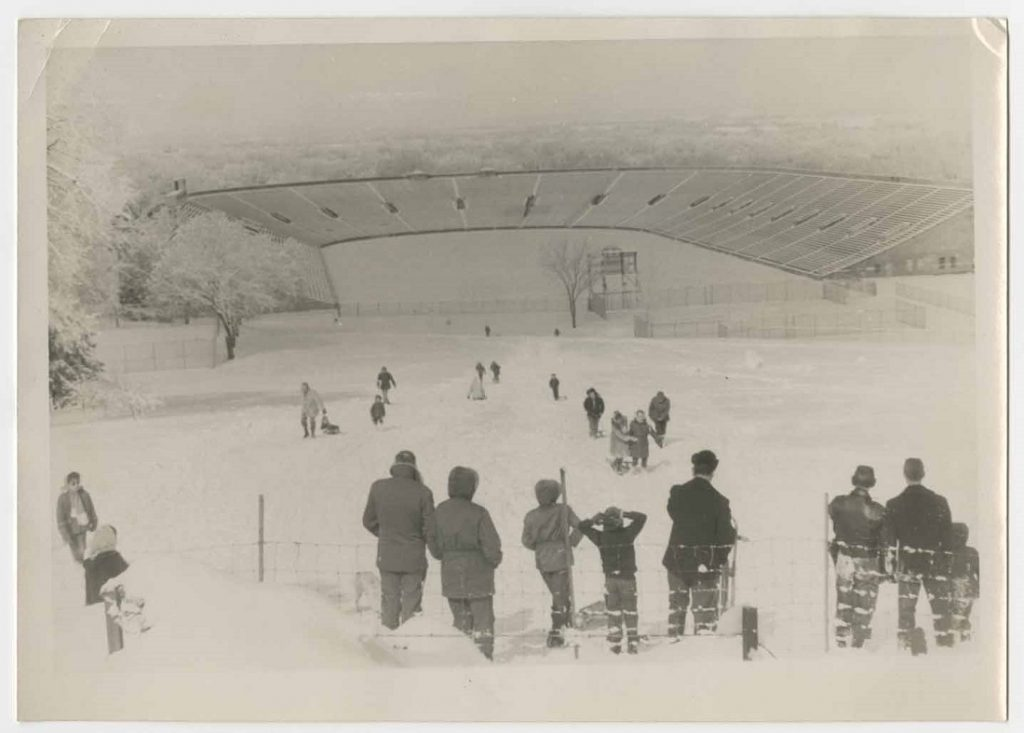 Photograph of people sledding toward Memorial Stadium, 1950s