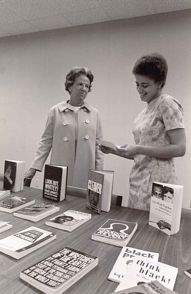 Photograph of Elizabeth Snyder and Betty Ann Bush examining Bush's book collection at the Snyder Book Collecting Contest, 1969