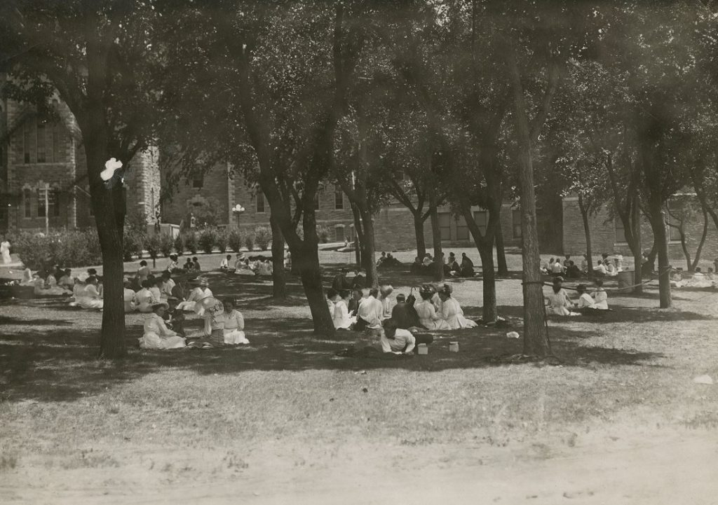 Photograph of students on the lawn in front of Old Fraser Hall, 1900s