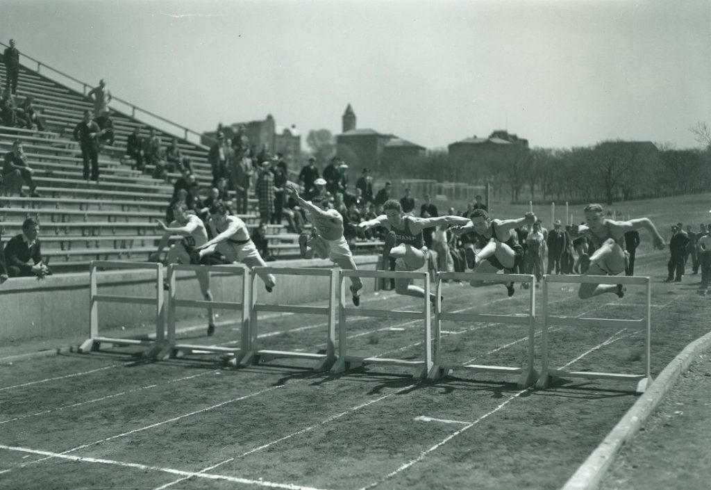 Photograph of six athletes running the hurdles at the Kansas Relays, 1936