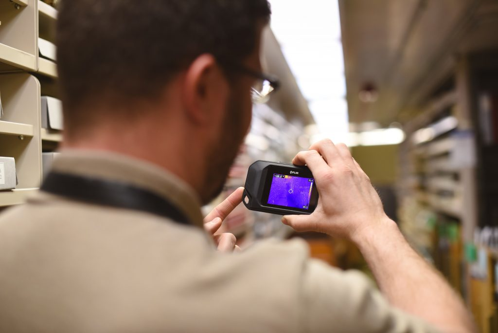Consultant using an infrared camera in the Spencer Library stacks, University of Kansas Libraries.