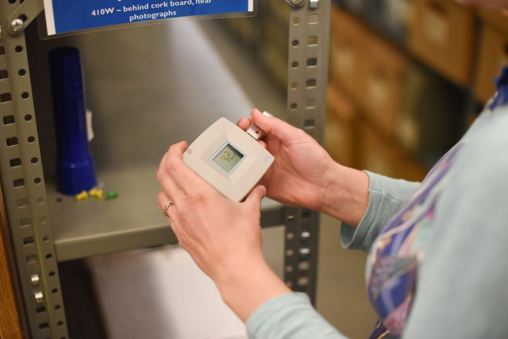 Consultant using a datalogger in the Spencer Library stacks, University of Kansas Libraries.