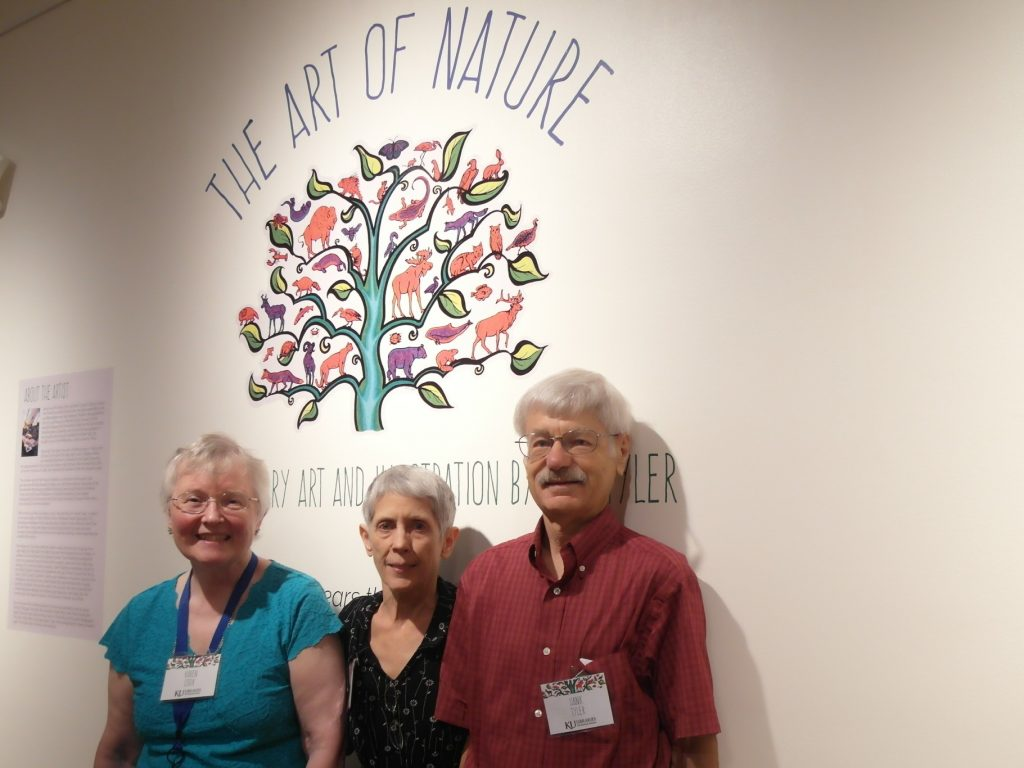 "Karen Cook, DD Tyler, and Hank Tyler in front of the main exhibition title for ""The Art of Nature,"" July 12, 2018"
