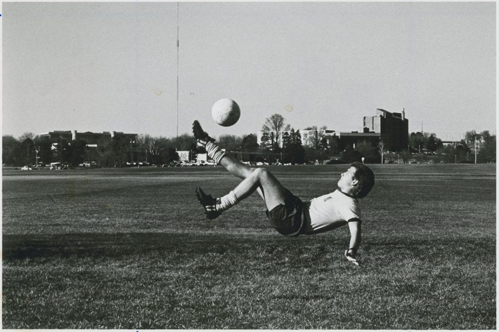 Photograph of a KU soccer player kicking a ball, 1986-1987