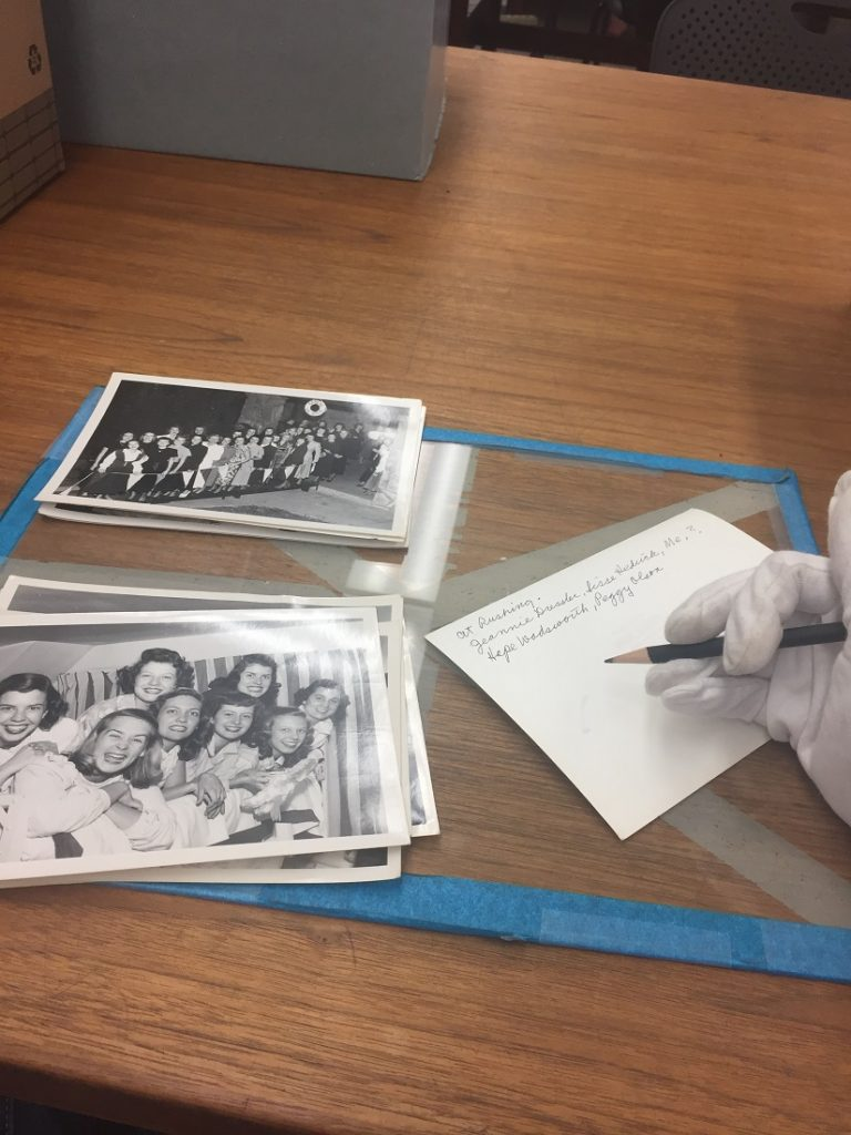 Photograph of Pi Beta Phi photographs being processed in University Archives