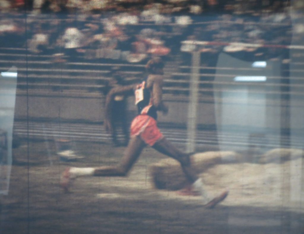 Film still of Wilt Chamberlain in the high jump event at the Kansas Relays, 1957