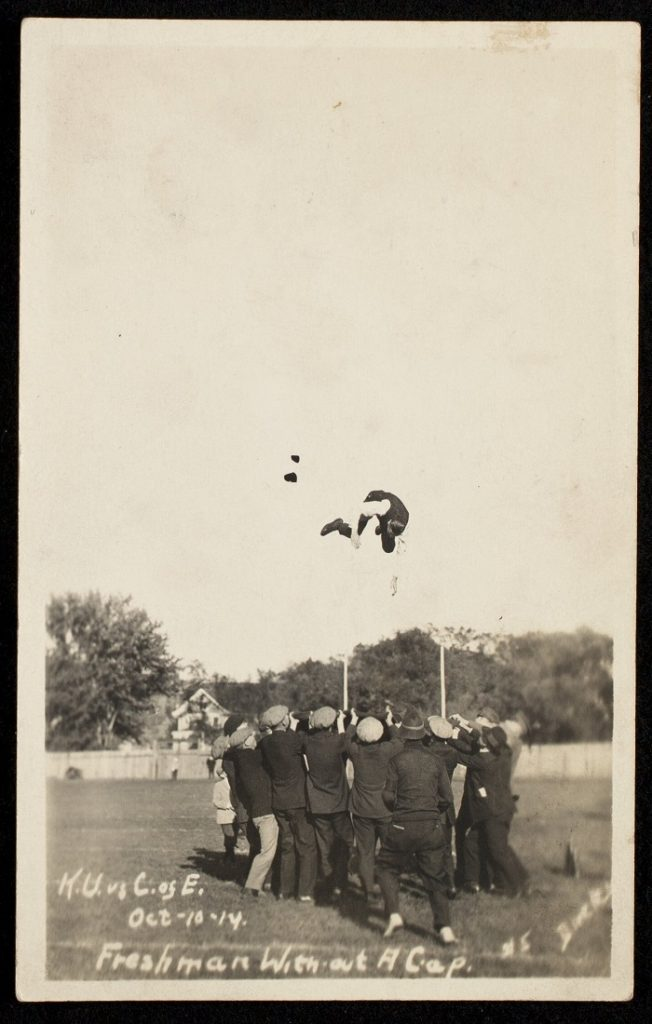 Photograph of a group of men tossing a freshman caught without his cap, 1914