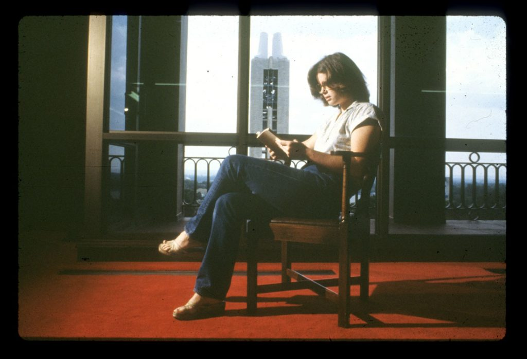 Photograph of a library student assistant reading a book in the North Gallery at Spencer Research Library, 1970s