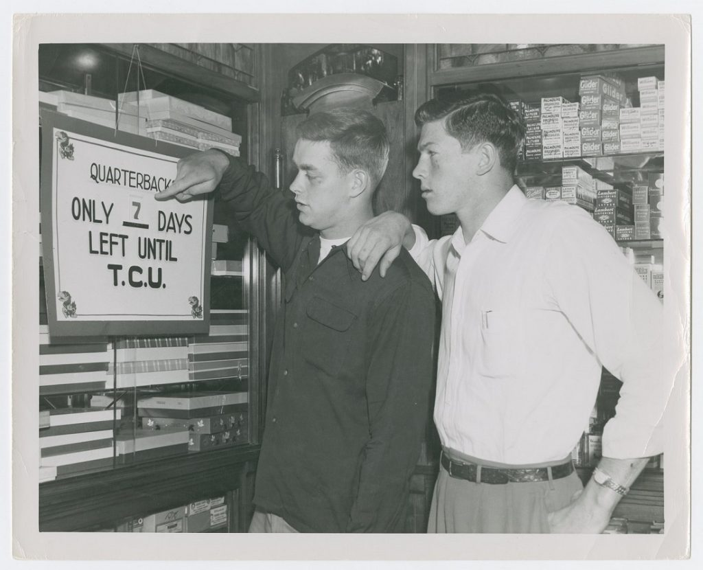 Photograph of two KU football players looking at a sign, 1951