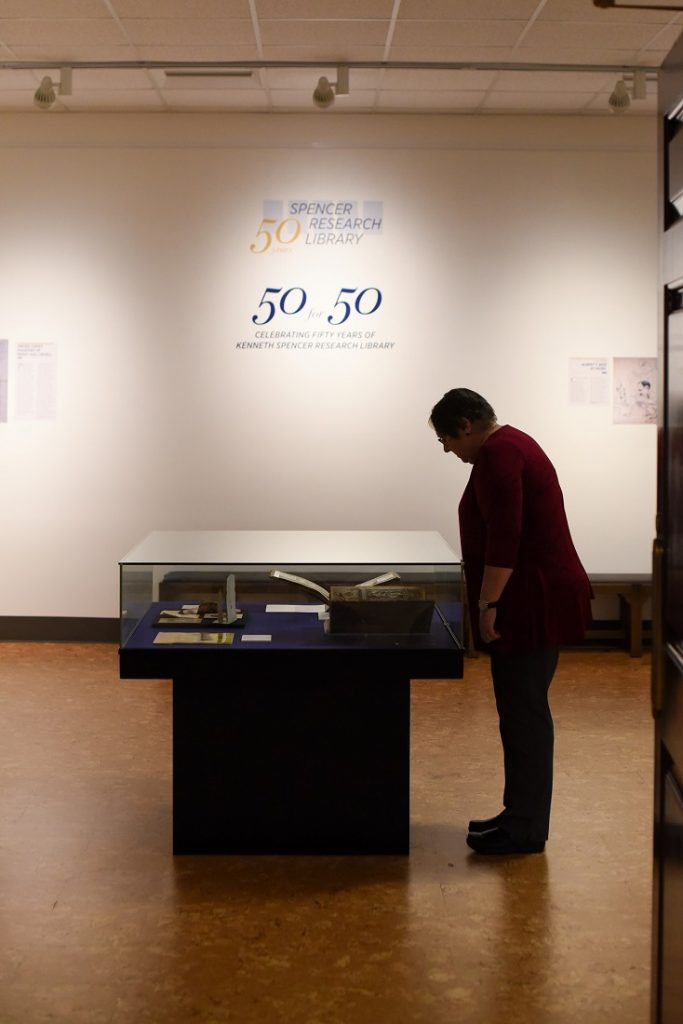 "Photograph of a guest exploring the ""50 for 50"" exhibit at Spencer Research Library's fiftieth anniversary celebration, 2018"