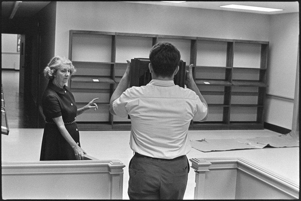 Photograph of Helen Spencer directing the placement of furniture at Kenneth Spencer Research Library, 1968
