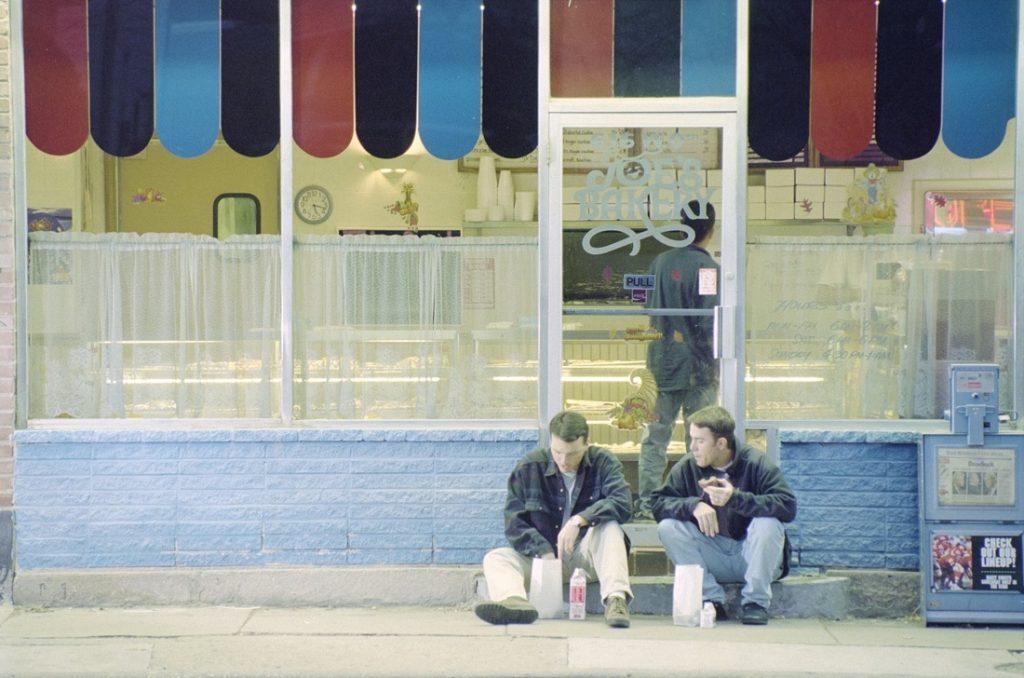 Photograph of two men sitting on the sidewalk outside Joe's Bakery, 1995