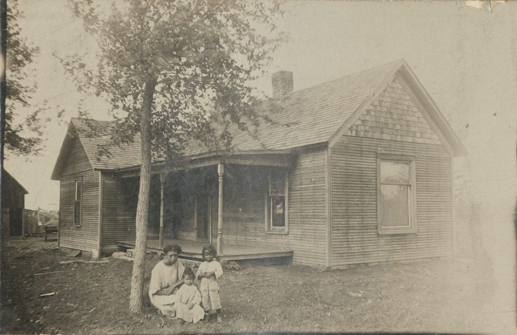 Photograph of Lenetta Scott with sons George and Luther Scott outside the family's home in Topeka, Kansas, 1915