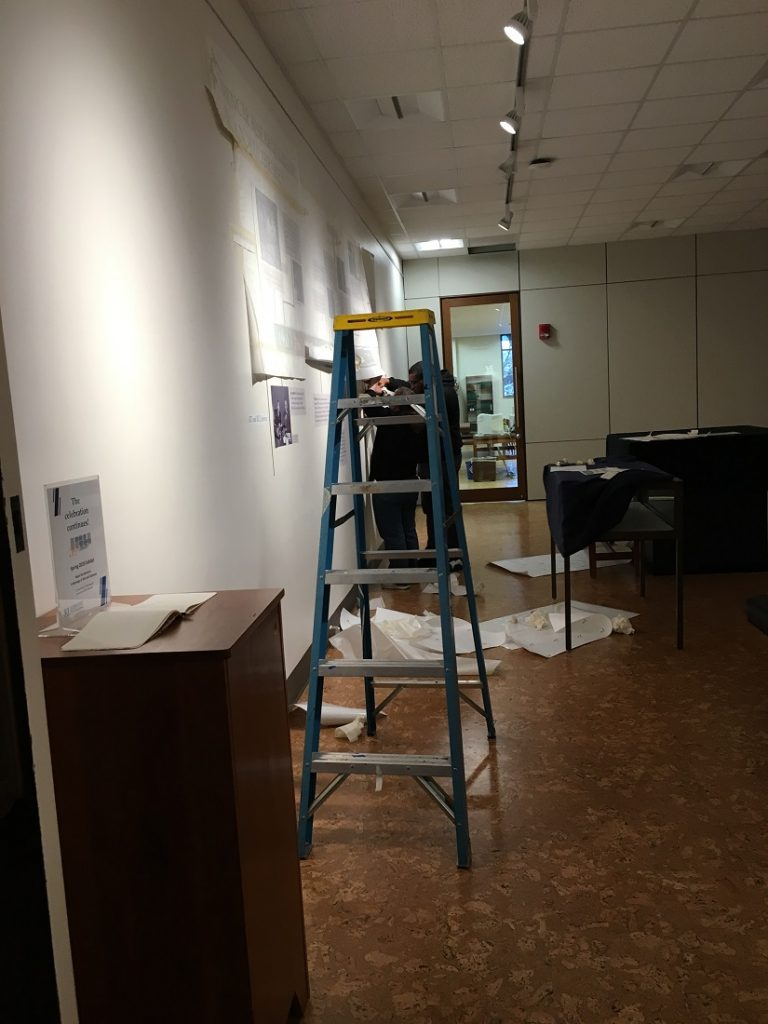 "Photograph of the installation of wall labels for the ""Meet the Spencers"" exhibit"