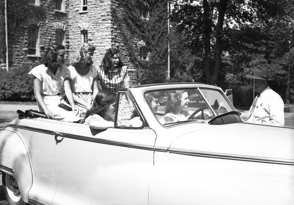 Photograph of women students in a car talking to an officer, 1940-1949
