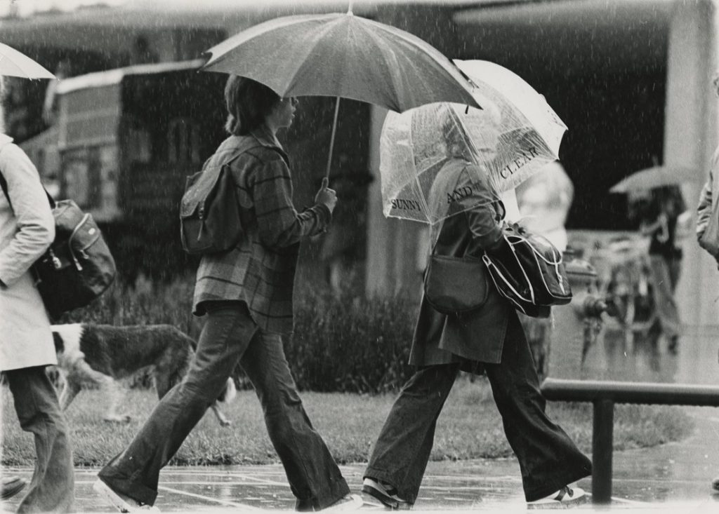 Photograph of KU students walking in the rain, 1976-1977