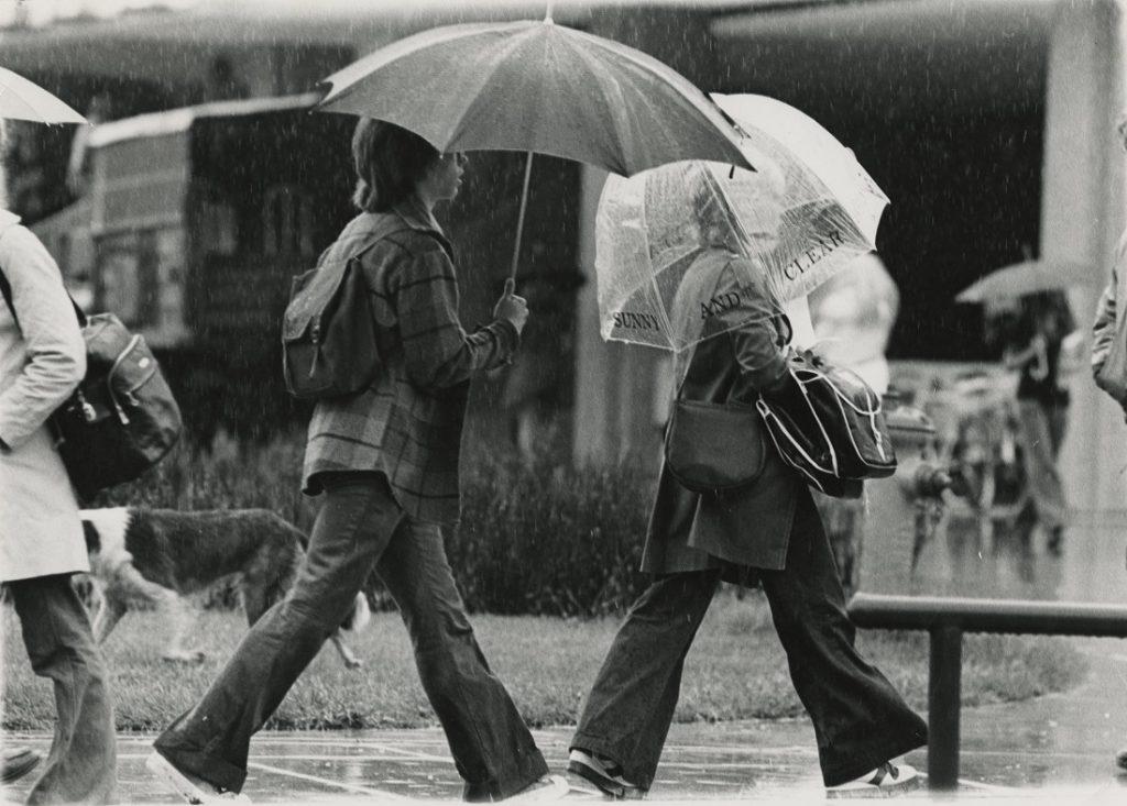 Photograph of KU students walking in the rain, 1976-1977