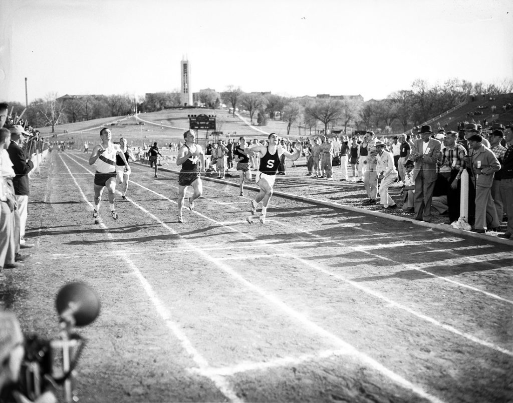 Photograph of athletes finishing a race at the Kansas Relays, 1956