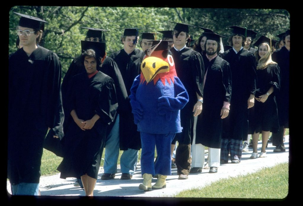Photograph of KU students and Baby Jay walking down the hill at Commencement, 1974