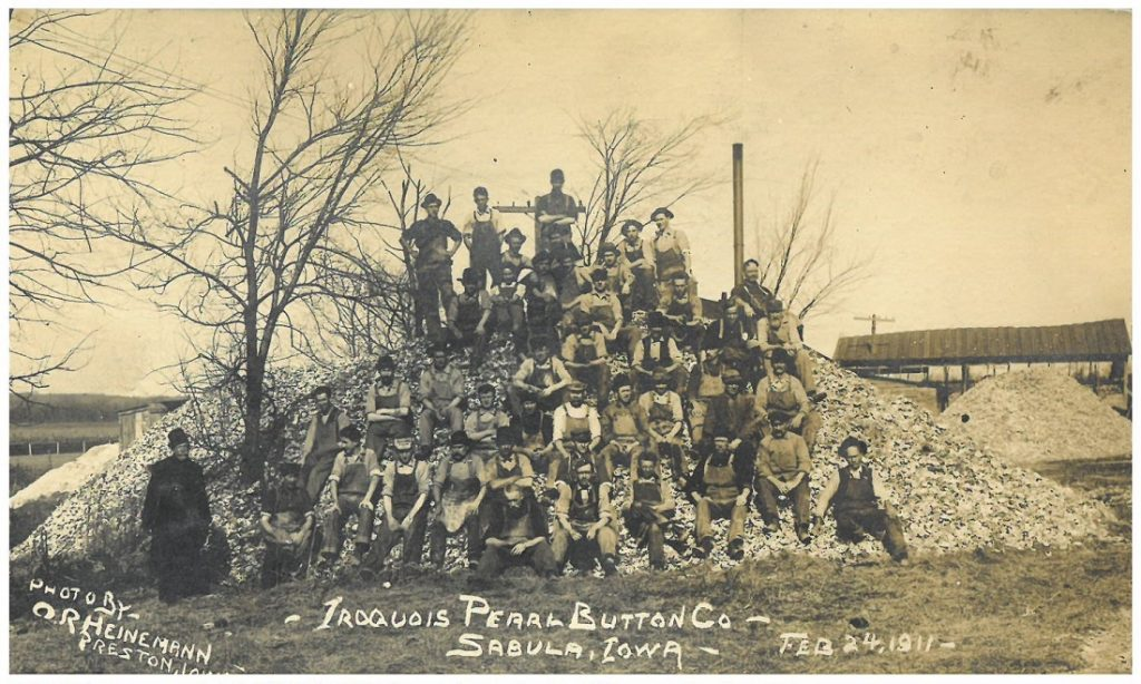 Men standing and sitting on what appears to be a large pile of buttons at the Iroquois Pearl Button Company in Sabula, Iowa, 1911