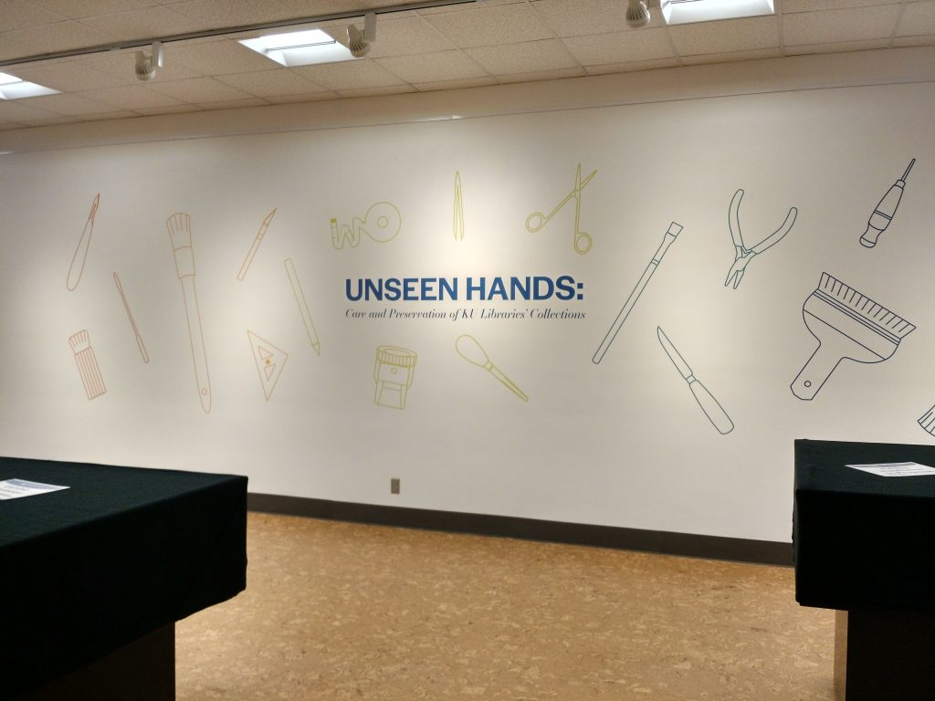 "Wall graphic for ""Unseen Hands"" exhibit at Kenneth Spencer Research Library, University of Kansas Libraries."
