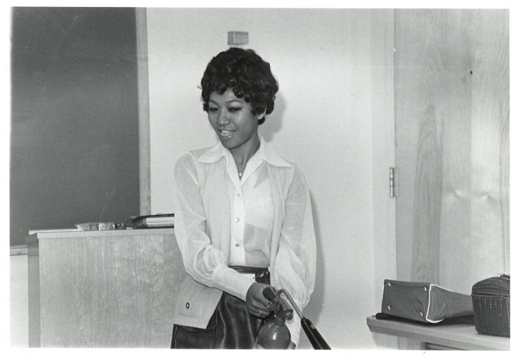 Photograph of a flight attendant student at the TWA Training School practicing with a fire extinguisher