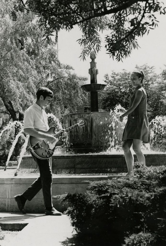 Photograph of a man playing a guitar as a woman watches from the Chi Omega Fountain, 1969-1970