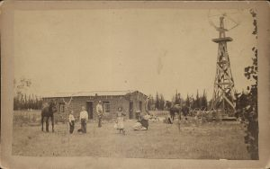 Cabinet card of a sod home with family. Photographer B. I. March