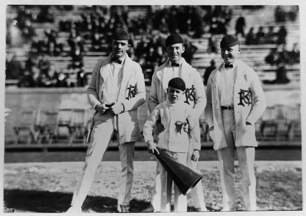 Photograph of three KU cheerleaders with a young boy, 1922-1923