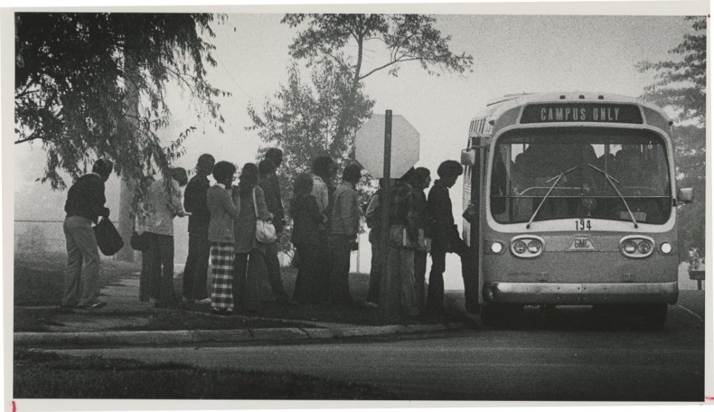 "Photograph of KU students boarding a ""campus only"" bus, 1975"