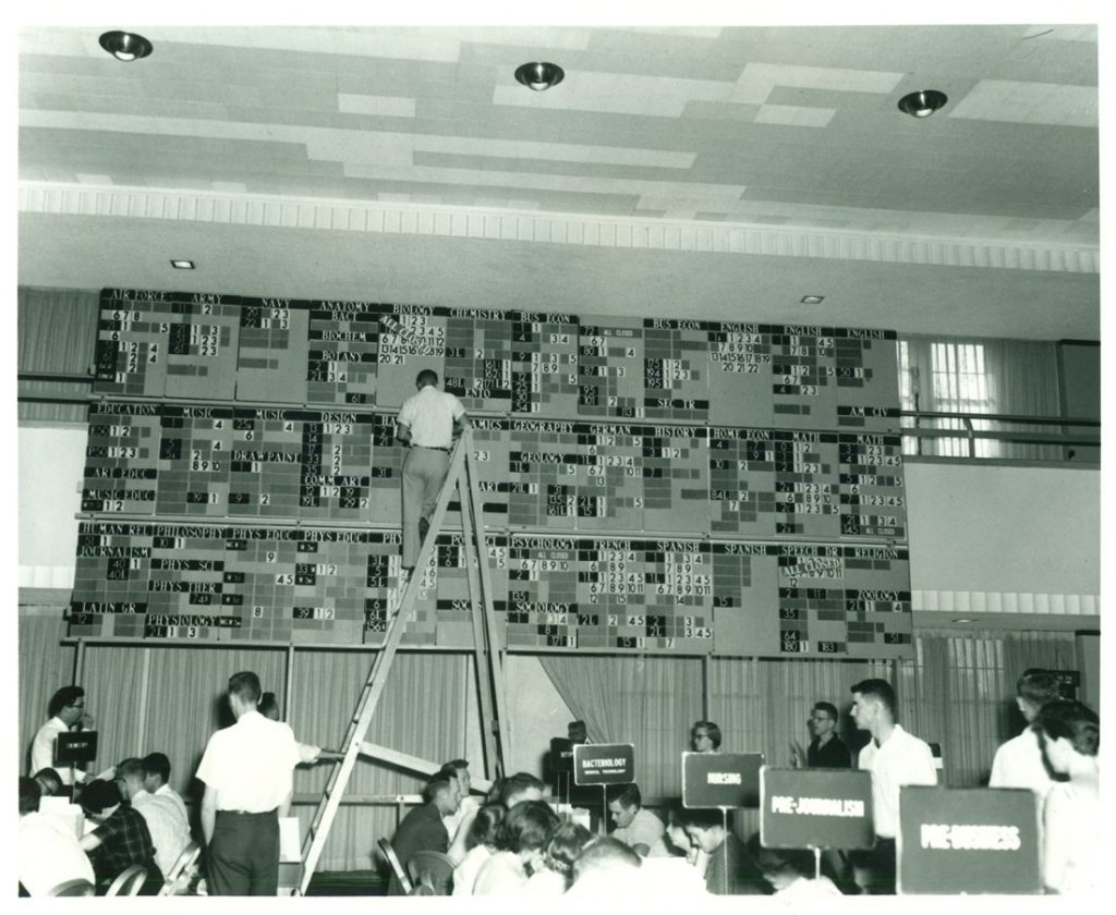 "Photograph of someone updating the ""enrollment bullpen,"" 1955"
