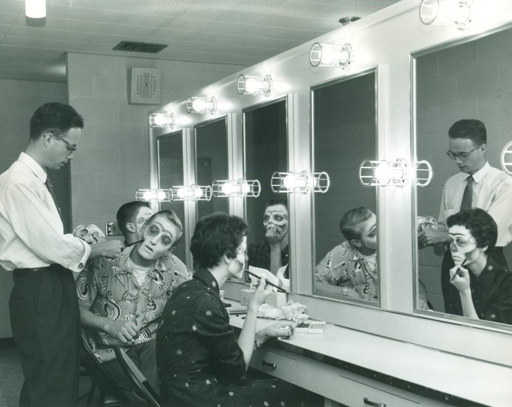 Photograph of Professor Jack Brooking with students practicing make-up application, 1950s